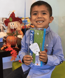 boy smiling holding new toothbrush
